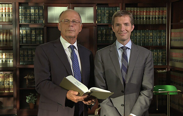 Andrew Walker and Curtis walker Minnesota Bankruptcy Attorneys standing in front of a bookcase with Curtis holding an open law book
